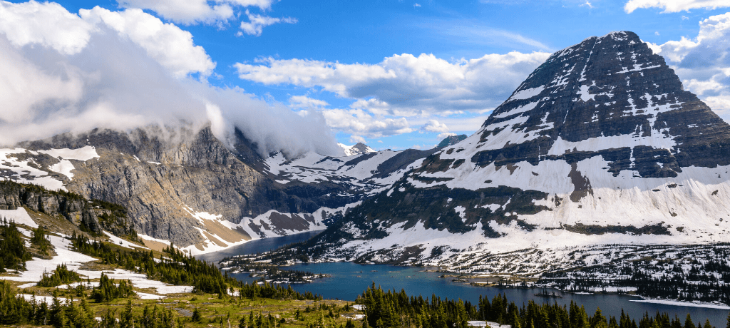 Beautiful view of snowcapped mountains and a teal lake in Glacier National Park